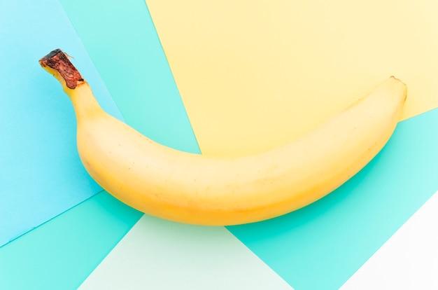 Banane jaune courbée sur une surface multicolore Photo gratuit