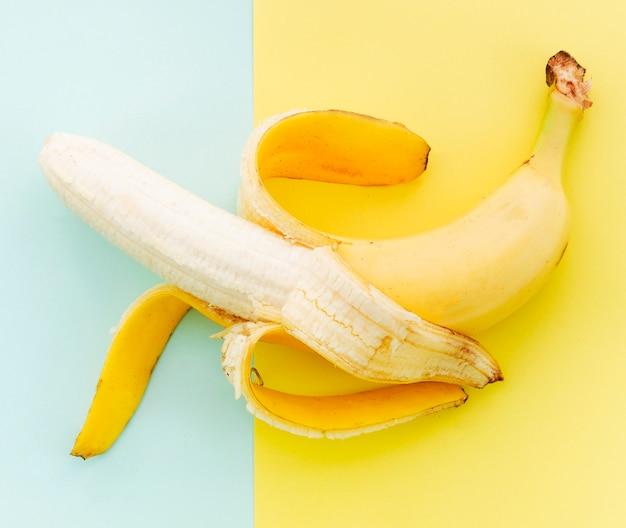 Banane pelée sur fond coloré Photo gratuit