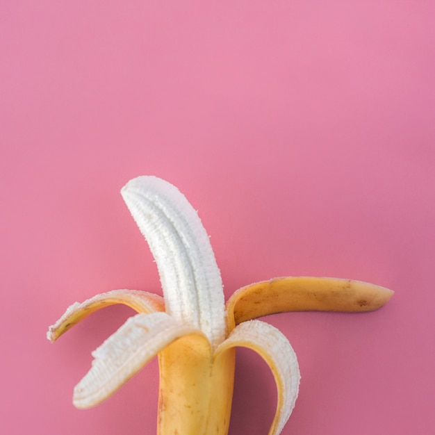 Banane pelée sur rose Photo gratuit