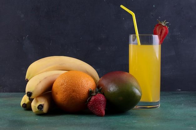 Bananes Vue De Face Avec Des Fraises Mangue-orange Et Un Verre De Jus D'orange Photo gratuit