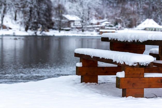 Banc En Bois Et Une Table Près Du Lac Entouré D'arbres Couverts De Neige Pendant L'hiver Photo gratuit