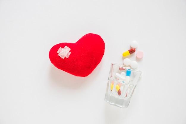 Bandage sur coeur rouge fourré de nombreuses pilules renversant du verre sur fond blanc Photo gratuit