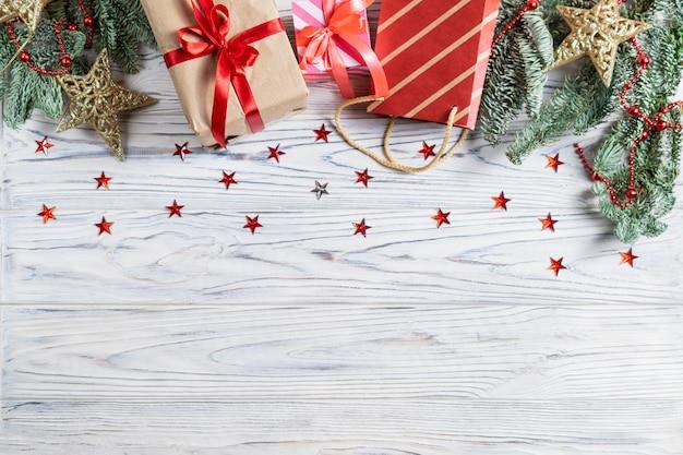 Bannière avec cristmas présente et décorations sur un fond en bois blanc avec des étoiles scintillantes Photo Premium