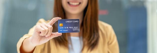 Bannière de femme asiatique tenant et présentant la carte de crédit pour les achats en ligne dans les grands magasins Photo Premium