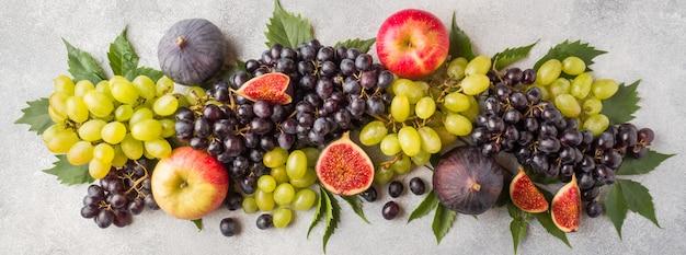 Bannière de fruits d'automne frais. des raisins noirs et verts, des figues et des feuilles sur une table grise. Photo Premium