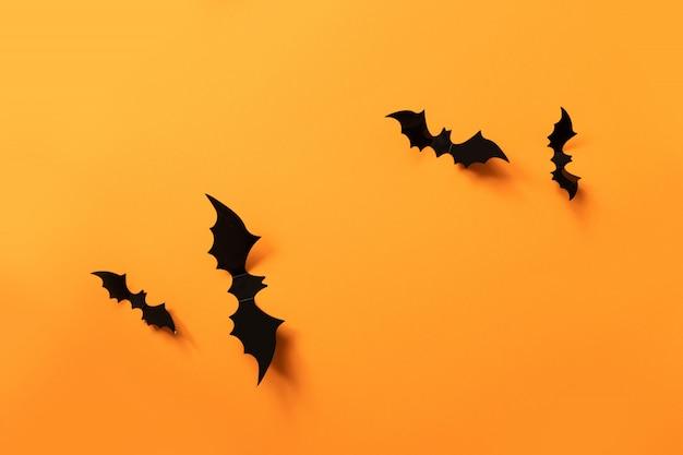 Bannière d'halloween avec des chauves-souris noires sur une surface orange, vue de dessus. Photo Premium