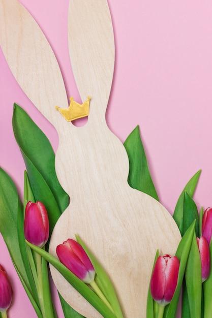 Bannière de pâques avec figure de lapin en bois et tulipes fraîches violettes. espace de copie pour le texte Photo Premium