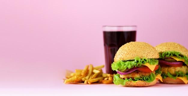 Bannière de restauration rapide. hamburgers de viande juteuse, pommes de terre frites français et boisson au cola sur fond rose. repas à emporter. concept de régime malsain Photo Premium