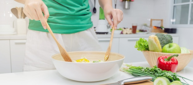 Bannière web. régime alimentaire jeune femme en chemise verte debout et préparant la salade de légumes dans un bol pour une bonne santé en cuisine moderne à la maison Photo Premium