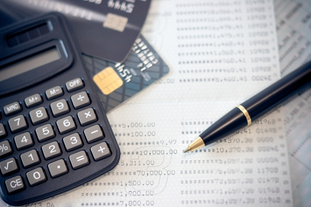 Banque de livre, cartes de crédit, la calculatrice, un stylo à bille. Photo Premium