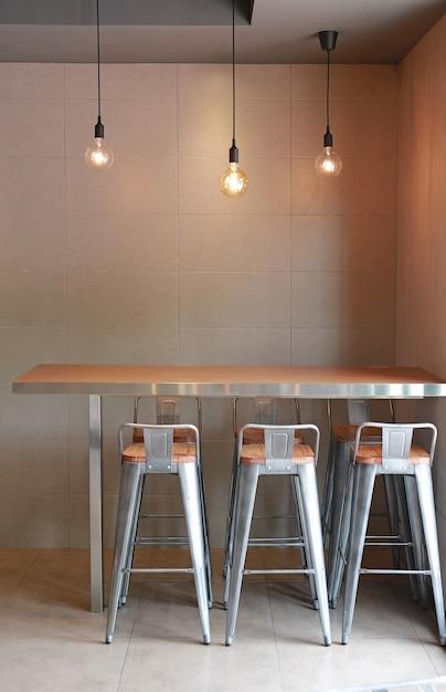 Bar de comptoir de table moderne avec un intérieur loft avec des chaises, un mur en carrelage gris et des lampes décoratives. Photo Premium
