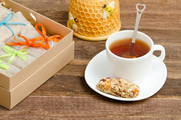 Bar de muesli, une tasse de thé et des boîtes avec des barres. petit-déjeuner sain Photo Premium