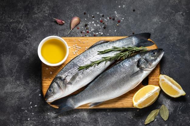 Bar de poisson frais et ingrédients pour la cuisine, citron et romarin Photo Premium