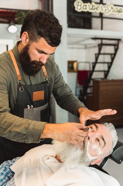 Barbe attentive rasage barbe au client dans un salon de coiffure Photo gratuit