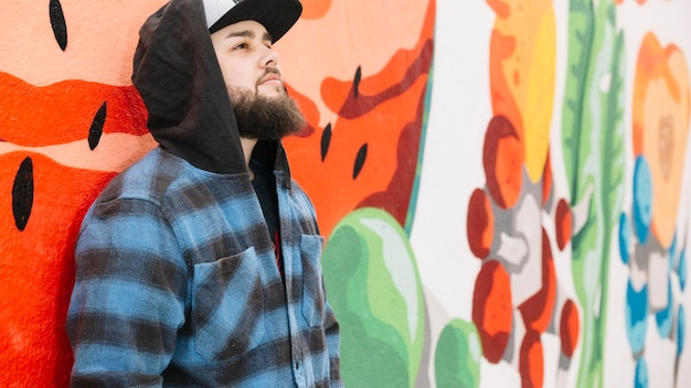 Barbe homme debout devant le mur de graffitis colorés Photo gratuit