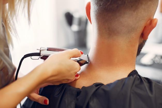 La barbe de l'homme rasant woma dans un salon de coiffure Photo gratuit