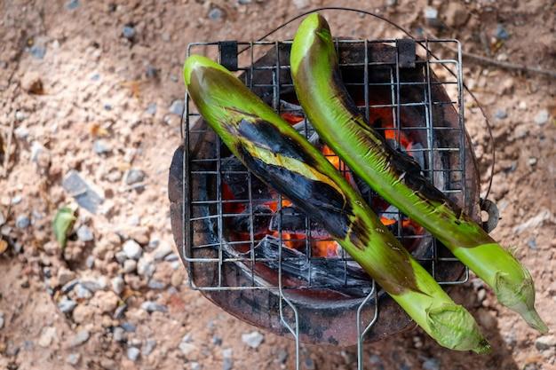 Barbecue long aubergines vertes grillées sur charbon de bois chaud. concept santé. la vie populaire. Photo Premium