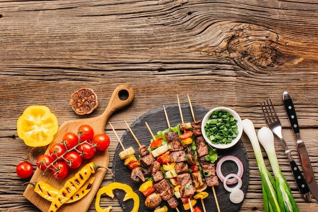Barbecue de poulet sur des brochettes de légumes sur un fond en bois Photo gratuit