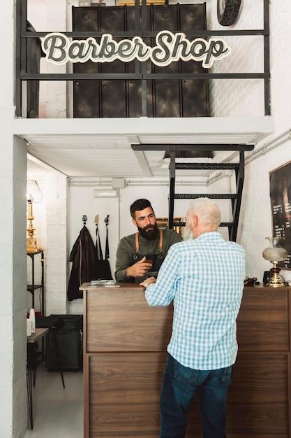 Barber en conversation avec le client à la réception Photo gratuit