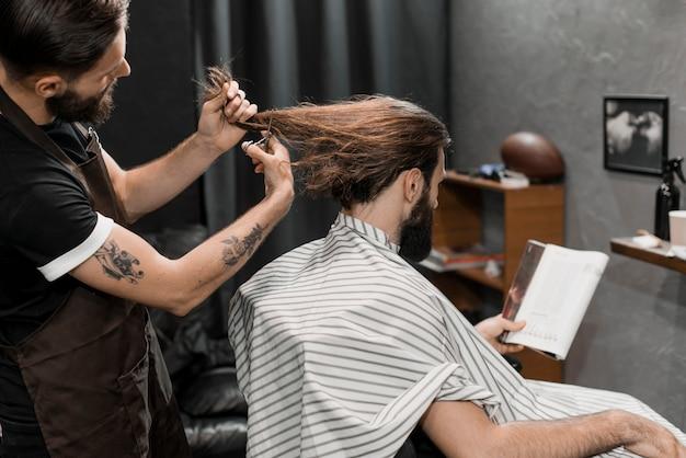 Barber coupe les cheveux longs de l'homme dans un salon de coiffure Photo gratuit