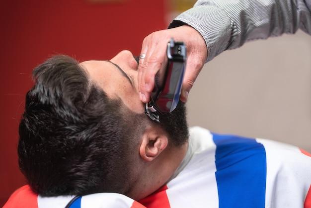 Barber rasant la barbe d'un bel homme barbu avec un rasoir électrique au salon de coiffure. Photo Premium