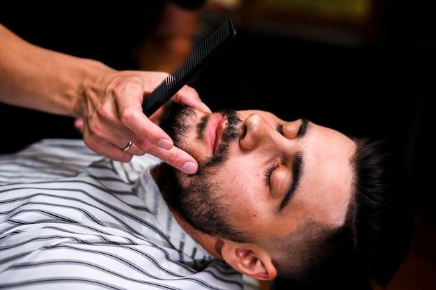 Barbier à angle élevé regardant la barbe du client Photo gratuit