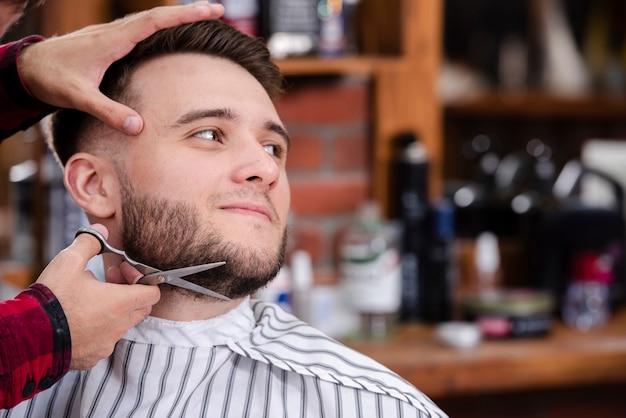 Barbier rasage barbe homme en salon de coiffure Photo gratuit