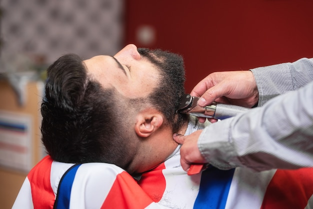 Barbier rasant la barbe d'un bel homme barbu avec un rasoir électrique au salon de coiffure. Photo Premium