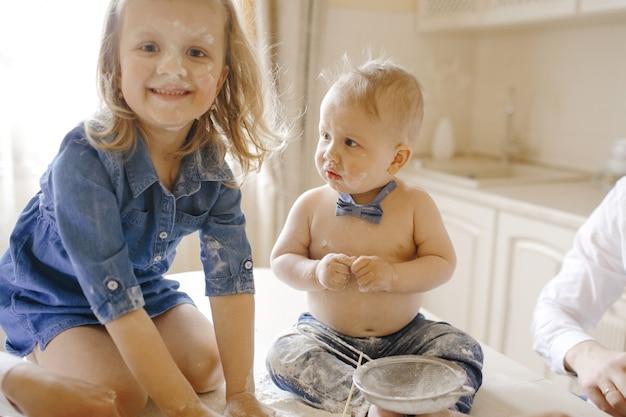 Barbouillé petit garçon et fille assise sur une table Photo gratuit