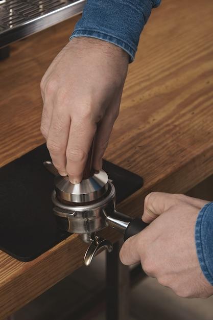 Barista à L'aide D'un Pilon Pour Presser Le Café Moulu Dans Un Porte-filtre Dans Un Café Sur Une Table En Bois épaisse Préparation Du Café Professionnel Photo gratuit