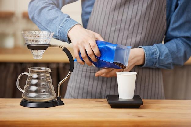 Barista Mâle Faisant Du Café Pouron, Mise à L'échelle Du Café Avec Une échelle Numérique. Photo gratuit