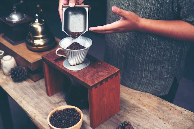Barista moud le café avec un moulin à café à la main. Photo Premium