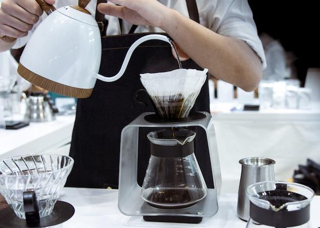 Barista préparant du café, barista versant du café goutte à goutte dans un verre Photo Premium