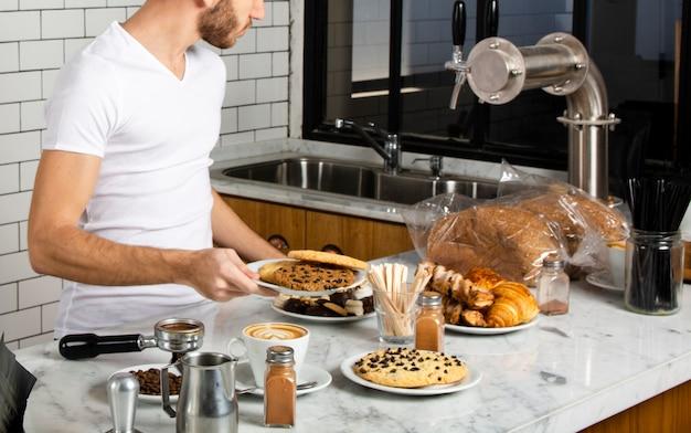 Barista tenant dans la main une assiette de biscuits Photo gratuit