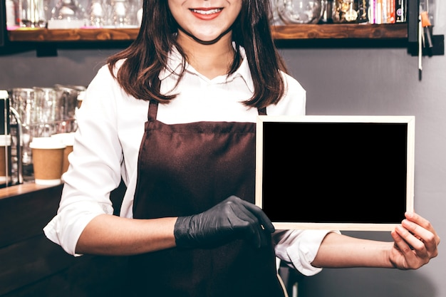 Barista tenant le tableau au café-restaurant Photo Premium