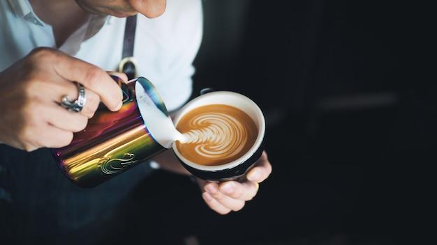 Barista versant du lait au café espresso latte art au café Photo Premium