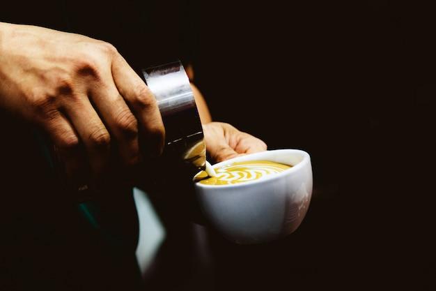 Barista versant du lait dans le café Photo Premium
