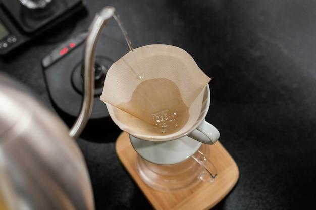 Barista Versant De L'eau Bouillante Dans Un Filtre à Café Photo gratuit