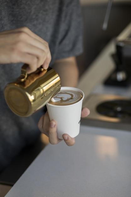 Barista Verser La Crème Dans Un Verre à Cappuccino Faisant Un Bel Art Du Café Photo gratuit