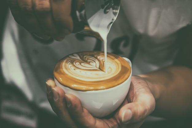 Barista, verser la mousse au lait pour faire un café au lait dans la tasse de café blanc Photo Premium
