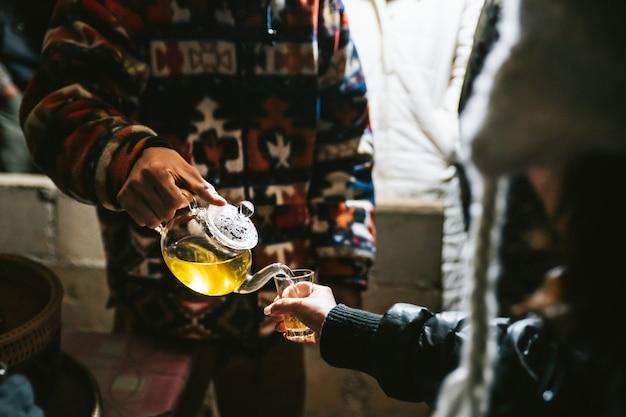 Barista verser le thé chaud à la camomille de la théière au verre à boire pour le testeur. Photo Premium