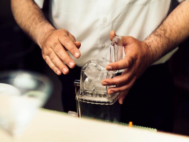 Barkeeper mettant la glace dans une boîte pour moudre Photo gratuit