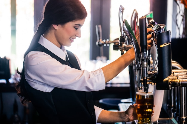 Barmaid servant une pinte dans un bar Photo Premium