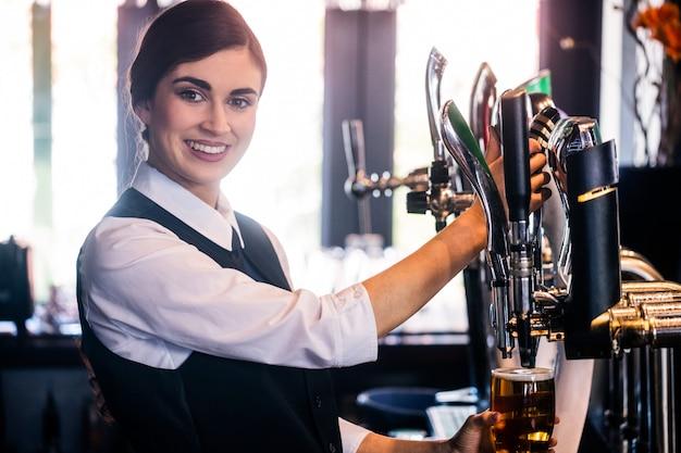 Barmaid servant une pinte dans un bar Photo Premium