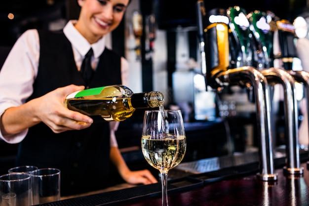 Barmaid servant un verre de vin dans un bar Photo Premium