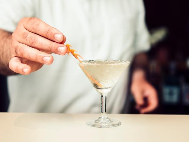 Barman ajoutant une décoration à un cocktail Photo gratuit
