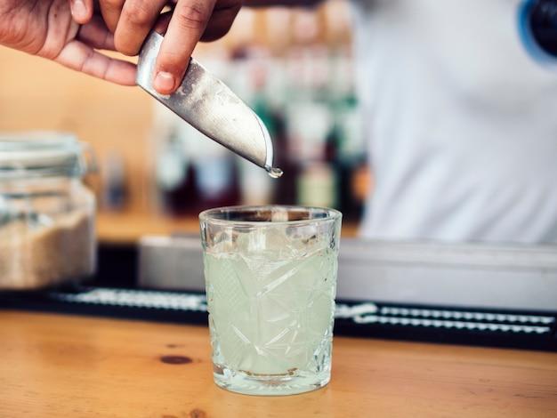 Barman ajoutant de la glace avec une cuillère Photo gratuit