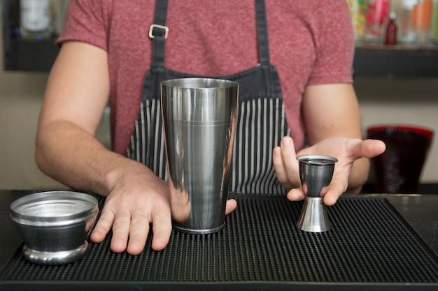 Le barman ajoute l'ingrédient dans le shaker au comptoir Photo gratuit