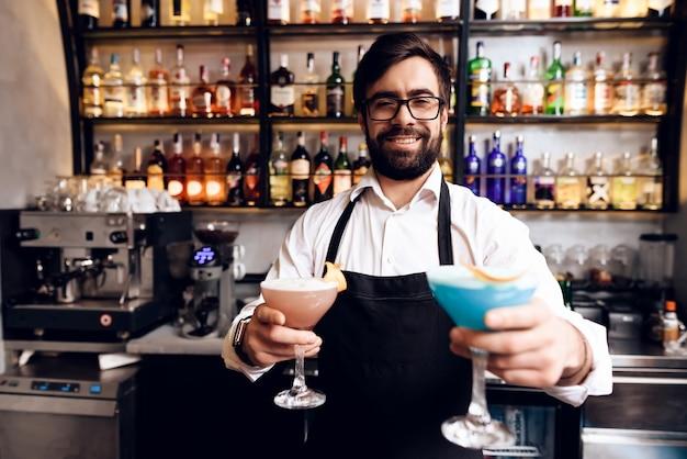 Le barman à la barbe prépara un cocktail au bar. Photo Premium