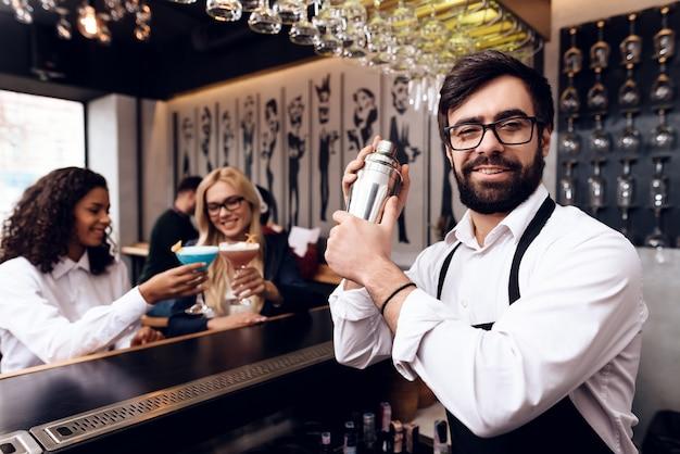 Un barman avec une barbe prépare un cocktail au bar. Photo Premium